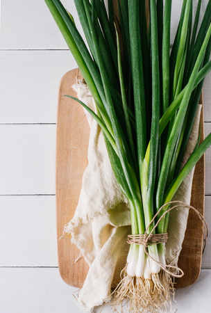 cebollines: Bunch of green young scallions with roots on a white background of old wooden boards vintage top view, healthy diet food, mock up kitchen table, leek of cooking process