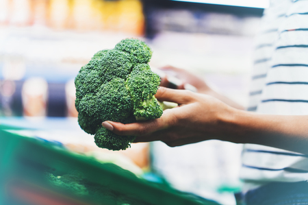 The buyer weighs the green fresh broccoli close up, woman shopping healthy food in supermarket blur background, female hands buy nature products in store grocery