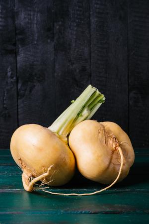 Turnips on a dark vintage dark wooden background closeup, agriculture diet food, fresh vegetable beetroot on kitchen table, mock up