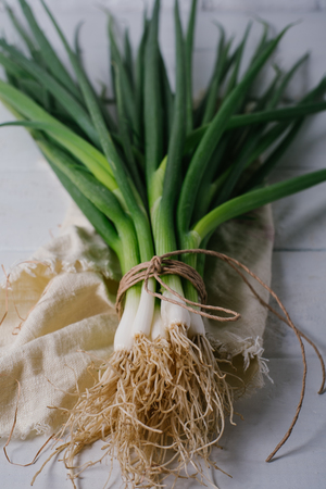 Bunch of green young scallions with roots on a white background of old wooden boards vintage top view, healthy diet food, mock up kitchen table, leek of cooking process, blur