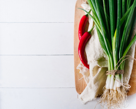 Bunch of green young scallions with roots on a white background of old wooden boards vintage top view, healthy diet food, mock up kitchen table, leek of cooking process