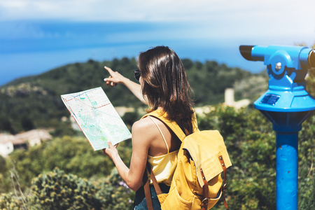 Hipster tourist hold and look map on trip, lifestyle concept adventure, traveler with backpack on background mountain and blue sea landscape horizon, young girl hiker pointing hands on trekking plan Stock Photo