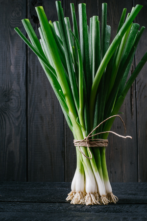 Bunch of green young scallions with roots on a black dark background of the old wooden boards vintage top view, agriculture concept, beetroot onion on cooking process on kitchen table, mock up