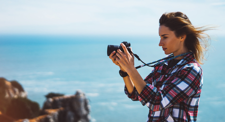Tourist traveler photographer making pictures sea scape on photo camera on background ocean, hipster girl looking on nature horizon, relax holiday, blank space blue waves view, blurred backdrop for text