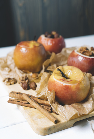Baked apples with cinnamon sticks and hazelnuts on parchment paper and cutting board on black wooden background Stock Photo