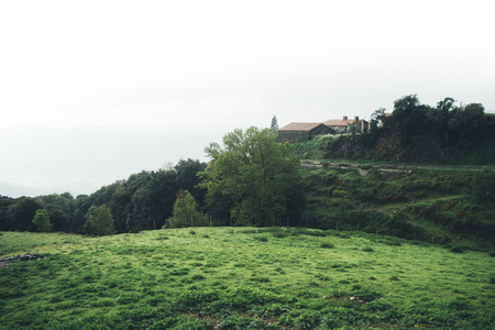 morning mist in the mountain peaks on natural landscape. Green valley on background foggy dramatic sky, house in  horizon perspective view of scenery hills Northern Spain. Travel mockup concept Stock Photo