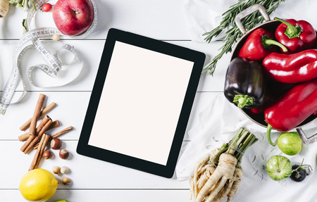 Tablet with a measuring tape, rosemary, lime, lemon, nuts, parsley root, tomatoes, cinnamon, peppers and red apples on a white wooden background top view horizontal