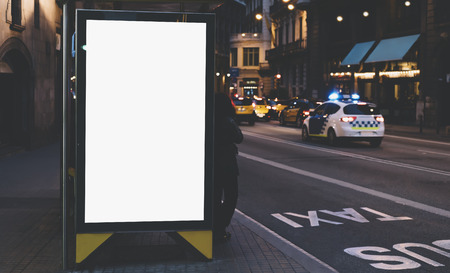 Blank advertising light box on bus stop, mockup of empty ad billboard on night bus station, template banner on background city street for poster or sign in Barcelona, afisha board and headlights of taxi cars Фото со стока