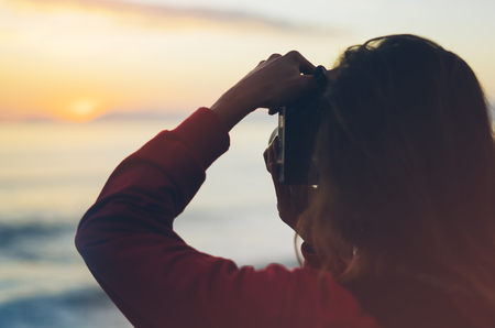 Hipster hiker tourist with backpack taking photo of amazing seascape sunset on camera on background blue sea, photographer enjoying ocean horizon, blurred panoramic sunrise blank mockup, traveler relax holiday concept, sunlight view in trip vacation northern spain
