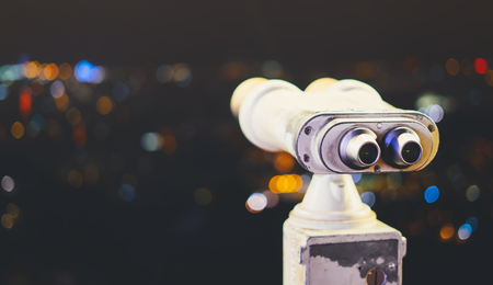 Touristic telescope look at city with view of Barcelona Spain, close up old metal binoculars on background viewpoint, hipster coin operated in panorama observation, mockup flare, illumination bokeh light in night blur atmospheric sky