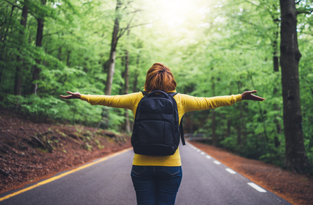 tourist traveler with backpack standing with raised hands, girl hiker view from back looking into road at forest with arms outstretched and enjoying the breath of fresh clean air in trip, relax holiday concept