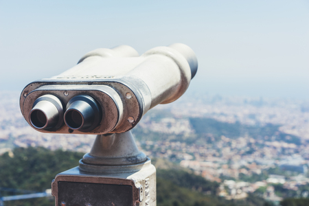 Touristic telescope look at the city with view of Barcelona Spain, close up old metal binoculars on background viewpoint overlooking the mountain, hipster coin operated in panorama observation nature blue sky, mockup