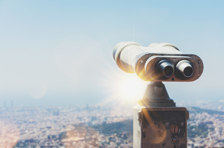 Touristic telescope look at the city with view of Barcelona Spain, close up old metal binoculars on background viewpoint overlooking the mountain, hipster coin operated in panorama observation nature blue sky, mockup flare