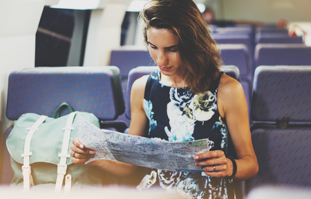 Enjoying travel. Young hipster smile girl with backpack traveling by train sitting near the window holding in hand and looking map. Tourist in summer shirt planing route of railway, railroad transport concept