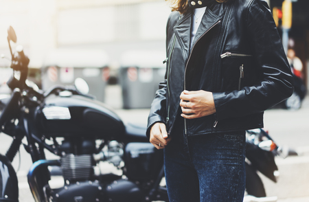 Girl unfastens black leather jacket on background motorcycle in sun flare atmospheric city, hipster biker female hands closeup, motorbike street lifestyle, traveler planing bike route in summer holiday concept Stock Photo