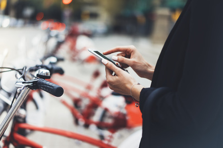 Young businesswomen in black  suit and umbrella using smartphone, biking and going to work by city bicycle on urban street, hipster girl holding mobile gadget, ecology environment concept Reklamní fotografie
