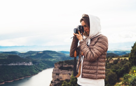 photographer traveler on green top on mountain, tourist looking holding in hands digital photo camera, hiker taking click photography, girl enjoy nature panoramic landscape in trip, relax holiday hobby concept 版權商用圖片