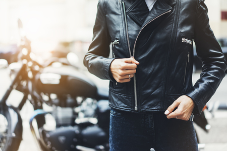 Girl unfastens black leather jacket on background motorcycle in sun flare atmospheric city, hipster biker female hands closeup, motorbike street lifestyle, traveler planing bike route in summer holiday concept Stok Fotoğraf