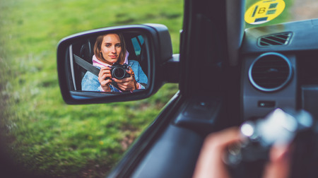 tourist girl in an open window of a car taking photography click on retro vintage photo camera, photographer looking on reflection in a mirror auto, blogger using hobby content concept, enjoy trip