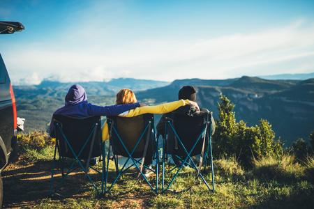 3人の友人が山の上のキャンプチェアに座り、旅行者は自然と抱擁を楽しみ、観光客はパノラマ風景、週末のコンセプトの背景に距離を見ます