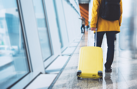 traveler tourist in bright jacket with yellow suitcase backpack at airport on background large window blue sky, man waiting in departure lounge area, hall of ​airport lobby terminal, vacation trip concept, empty space mockup 免版税图像