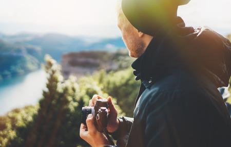 힙스터 관광객은 자동으로 복고풍 빈티지 사진 카메라를 클릭하고 카메라 기술, 취미 콘텐츠, 태양 플레어 산, 탁 트인 풍경 휴가 개념을 보고 있는 사진 작가를 손에 들고 있습니다. 스톡 콘텐츠