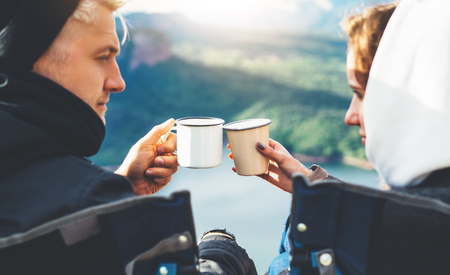 lovers looking at each other, couple enjoy together of sun flare mountain, travelers drink tea on cup enjoy nature, romantic look on background of panoramic landscape, weekend concept