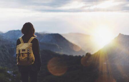 Hipster junges Mädchen mit hellem Rucksack, der den Sonnenuntergang auf dem Gipfel des nebligen Berges genießt. Touristischer Reisender auf Tallandschaftsansichtsmodell im Hintergrund. Wanderer auf der Suche nach Sonnenlicht auf der Reise im Baskenland Nordspaniens, Mock-up für Text. Picos de Europa