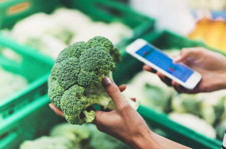 Young woman shopping healthy food in supermarket blur background. Female hands buy products broccoli using smartphone in store. Hipster at grocery using smartphone. Person comparing price of produce Zdjęcie Seryjne
