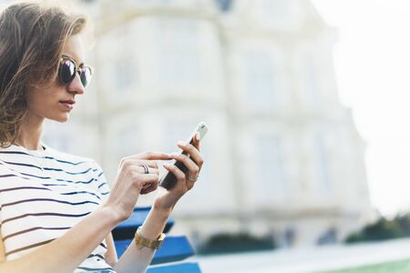 Hipster texting message on smartphone or technology, mockup of blank screen. Girl using cellphone on building castle background close. Tourist female hands holding gadget on blurred summer backdrop