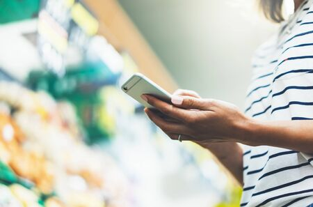 Young woman shopping healthy food in supermarket blur background. Female hands buy products tomato using smartphone in store. Hipster at grocery using smartphone. Person comparing price of produce Zdjęcie Seryjne
