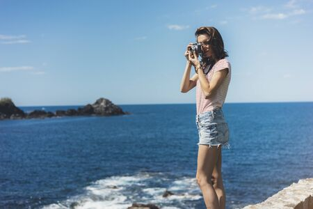 Tourist traveler photographer making pictures sea scape on vintage photo camera on background yacht and boat piar, hipster girl enjoying peak mountain and nature holiday, mockup ocean waves view, blurred backdrop Banco de Imagens