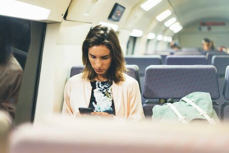 Enjoying travel. Young pretty woman traveling by train sitting near the window using smartphone and looking map. Tourist texting online message and plan route of railway, railroad transport concept