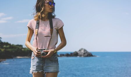 Tourist traveler photographer making pictures seascape on vintage photo camera on background yacht and boat piar, hipster girl enjoying peak mountain and nature holiday, mockup ocean waves view, blurred backdrop 版權商用圖片 - 130796600