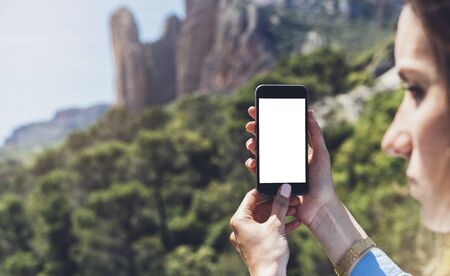 Hipster girl making photo on smartphone mobile closeup, view tourist hands using gadget phone in travel on background mountains and sky landscape; finger touch screen cellphone mockup nature, templates