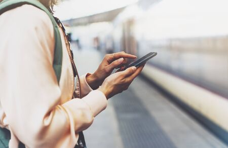 Enjoying travel. Young pretty woman waiting on the station platform with backpack on background electric train using smartphone. Tourist texting message and plan route of railway, railroad transport concept Stockfoto
