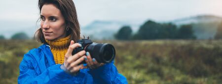 photographer tourist girl in blue raincoat hold in female hands photo camera take photography froggy mountain, traveler shooting autumn nature, click on camera technology, journey landscape vacation hobby concept free space 스톡 콘텐츠 - 129756688
