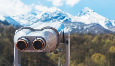 touristic telescope look at the city with view snow mountains, closeup binocular on background viewpoint observe vision, metal coin operated in panorama observation, travel nature concept Reklamní fotografie