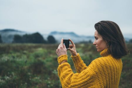 photographer girl hold in hands mobile phone taking photo on smartphone autumn froggy mountain, tourist shooting on photo camera on background landscape, internet online concept 스톡 콘텐츠