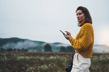 photographer girl hold in hands mobile typing message on smartphone on background landscape autumn froggy mountain, tourist shooting on photo camera using mobile gadget, internet online concept