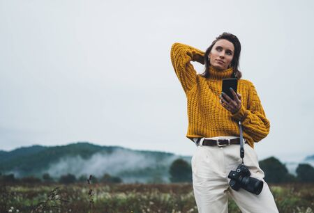 photographer girl hold in hands mobile typing message on smartphone on background landscape autumn froggy mountain, tourist shoot on photo camera using internet online gadget, hobby concept 스톡 콘텐츠 - 129756778