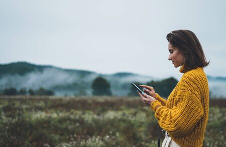 photographer girl hold in hands mobile phone typing message on smartphone on background autumn froggy mountain, internet online concept