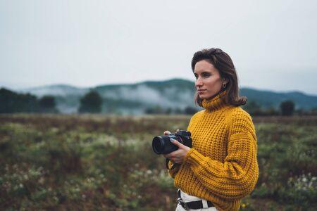 photographer girl take photo on camera on background autumn froggy mountain, tourist enjoy nature mist landscape, hobby concept, copy space 스톡 콘텐츠