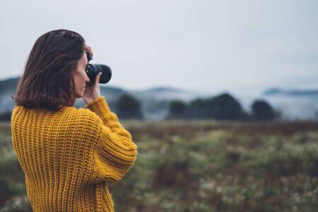 photographer traveler take photo on video camera closeup on background autumn froggy mountain, tourist shooting nature mist landscape 스톡 콘텐츠 - 129756788