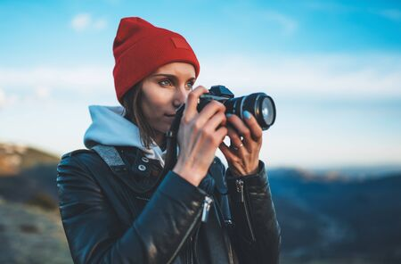 hipster tourist girl hold in hands take photography click on modern photo camera, photographer look on camera technology, journey landscape vacation concept, sun flare mountain 스톡 콘텐츠 - 129756790