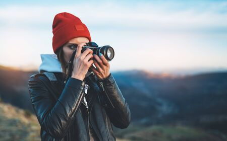 hipster tourist girl hold in hands take photography click on modern photo camera, photographer look on camera technology, journey landscape vacation concept, sun flare mountain