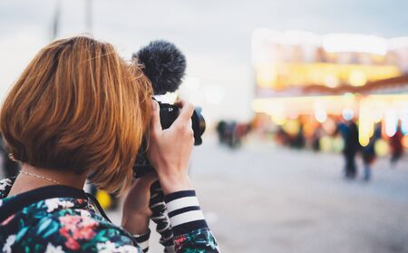 hipster tourist girl hold in hands modern photo camera, take photography click on defocus background bokeh light in evening street attraction, photographer look on camera technology, night city illumi 스톡 콘텐츠