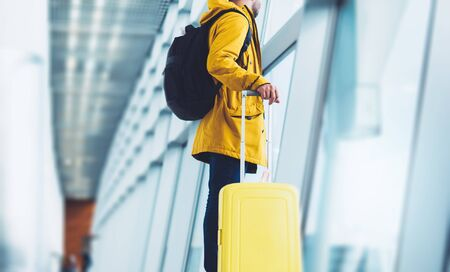traveler tourist in bright jacket with yellow suitcase backpack at airport on background large window blue sky, man waiting in departure lounge area, hall of ​airport lobby terminal, vacation trip concept, empty space mockup