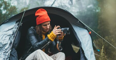 photographer tourist traveler take photo on camera in camp tent in froggy rain forest, hiker woman shooting mist nature trip, green trekking tourism, rest vacation concept camping holiday