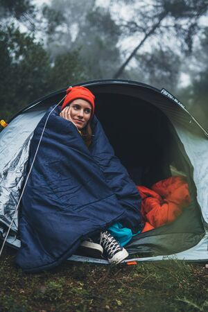 tourist traveler smile ralaxing in camp tent in froggy mist forest, lonely happy hiker woman enjoy nature trip, green trekking tourism, rest vacation concept camping holiday